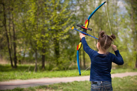 arco y flecha: Archer linda chica con el disparo arco en día soleado de verano. Lanzamientos de la niña del arco en el parque. Al aire libre. Las actividades deportivas con niños. El deporte y el concepto de estilo de vida. Apuntar alto Foto de archivo