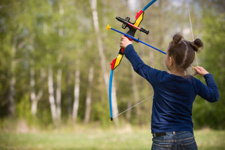 귀여운 소녀 아처 화창한 여름 날 촬영 활. 어린 소녀 공원에서 활을 촬영합니다. 옥외. 아이들과 함께하는 스포츠 활동. 스포츠 및 라이프 스타일 개념