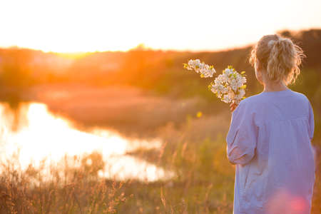 Back view on young woman by the lake on the sunset. Girl with apple trees flowers enjoying summer sunset in the park. Happy woman with bouquet, outdoors. Lifestyle and happiness concept Stock Photo