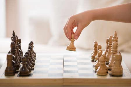 근접 촬영의 소년의 손에 체스 게임을하는 동안 체스 피규어를 잡고. 작은 영리한 자식 체스 가정에서. 교육 개념입니다.