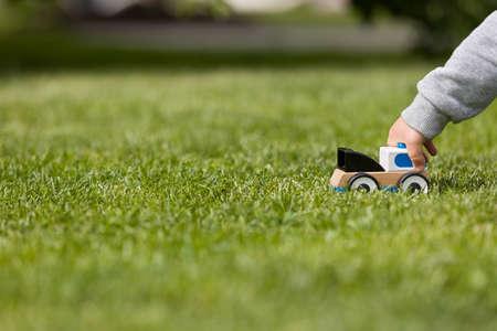 공원에서 푸른 잔디에 장난감 cay 재생 아이의 손 확대 사진. 작은 차를 가지고 노는 유아 소년. 보육 및 보육. 옥외. 어린 시절 및 라이프 스타일 개념입 스톡 콘텐츠