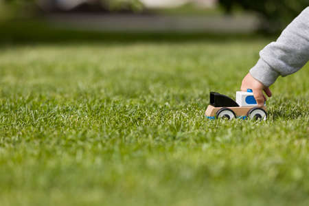 Closeup of childs hand playing with toy cay on the green grass in the park. Toddler boy playing with small car. Daycare and nursery. Outdoors. Childhood and lifestyle concept. Activities for children