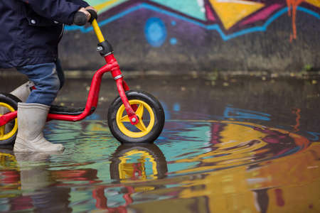 autumn rain: Little child in grey rubber boots cycling after rain.Toddler in a pair of grey rubber boots in a big puddle with grafiti wall reflection. Fun after rain. Boy on the bike on the street. Stock Photo