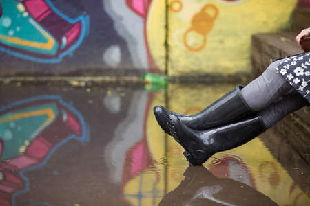 rubber: Woman in grey rubber boots sitting on the bench after rain. Pair of grey rubber boots in a big puddle with grafiti wall reflection. Fun after rain.