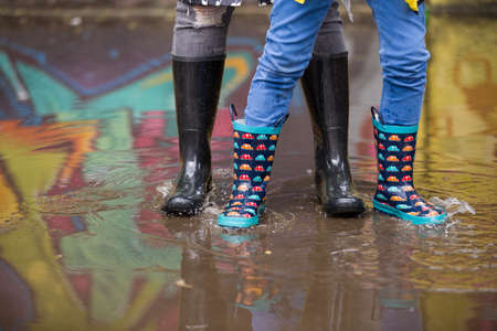 Kid boy and woman in funny rubber boots standing in the puddle in the street after rain. Family in colorful rubber boots in a big puddle with graffiti reflections - having fun after rain. Outdoor. Standard-Bild