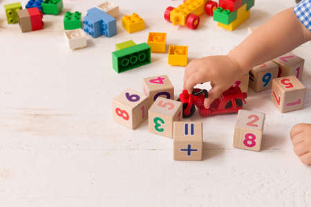 Close up of childs hands playing with colorful plastic bricks and red motocicle at the table. Toddler having fun and building out of bright constructor bricks. Early learning.   Developing toys