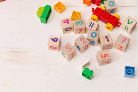 Top view on wooden cubes with numbers and colorful plastic bricks on white wooden table background. School, education and learning concept. 写真素材