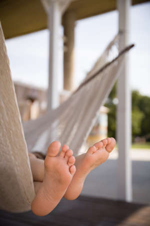 bare feet boys: Foot of a child lying in the hammock and relaxing on a sunny day. Bare feet. Lifestyle concept.