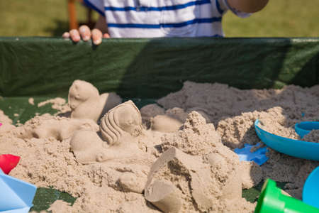 kinetic: Playground with kinetic sand outdoors. Child playing with shapes.