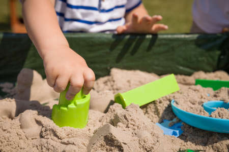 kinetic: Toddlers hands playing with kinetic sand outdoors. Child making shapes.  Lifestyle and summer concept. Stock Photo