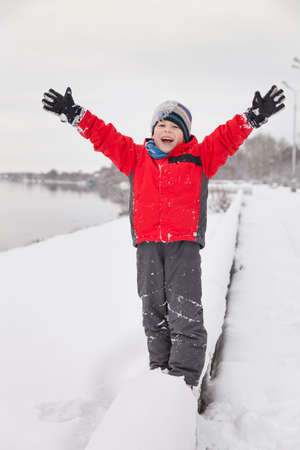 Portarit of cute preschool kid boy playing with snow and having fun in the park. Child with hands up on a cold winter day outdoors. Stock Photo