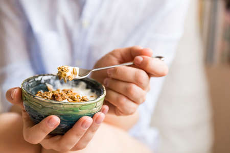 Young woman with muesli bowl. Girl eating breakfast cereals with nuts, pumpkin seeds, oats and yogurt in bowl. Girl holding homemade granola. Healthy snack or breakfst in the morning..