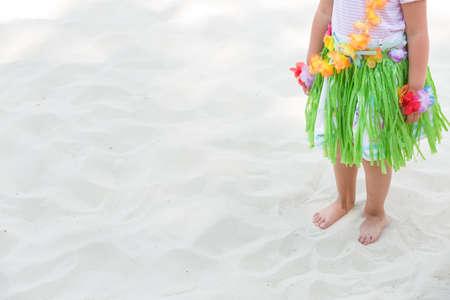 화창한 날에 모래에 서 하와이 복장에서 귀여운 작은 아이 소녀. 여름 개념입니다. 스톡 콘텐츠