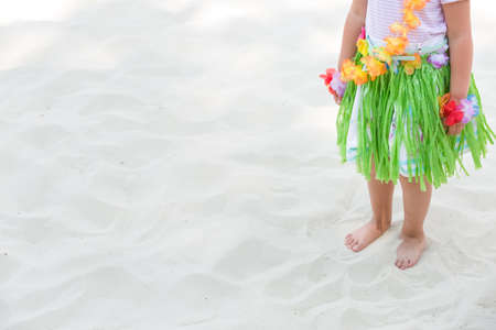 Cute little toddler girl in Hawaiian outfit standing on the sand on a sunny day. Summer concept.