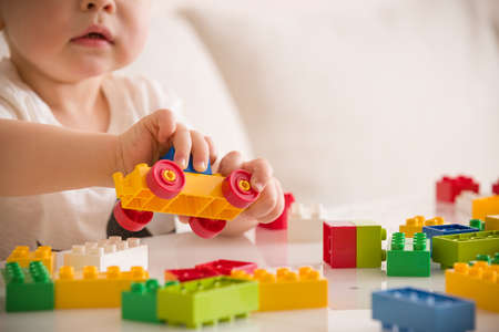 Close up of childs hands playing with colorful plastic bricks at the table. Toddler having fun and building out of bright constructor bricks. Early learning.  stripe background. Developing toys