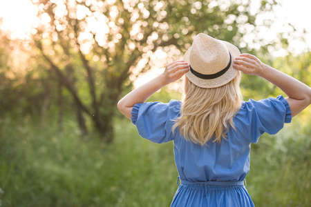 Back view on blond woman in beautiful blue dress holding straw hat in her hands and having fun in the park outdoors. Girl walking in the park on sunset. Lifestyle and summer concept.