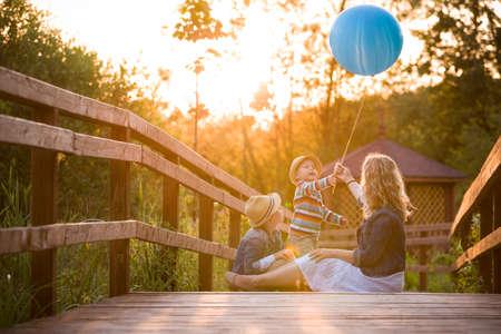 아이가 소년과 귀여운 작은 아이 나무 다리에 앉아 및 여름 일몰에 파란 풍선 놀고 어머니. 야외에서 아이들과 함께 여자입니다. 라이프 스타일 컨셉