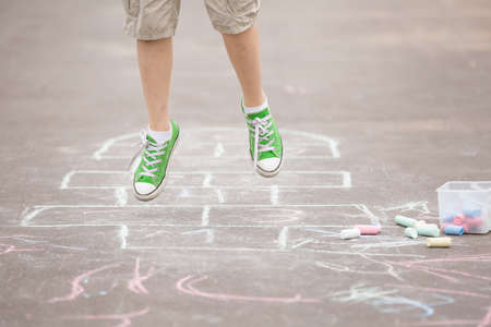 hopscotch: Closeup of boys legs and hopscotch drawn on asphalt. Child playing hopscotch on playground outdoors on a sunny day. outdoor activities for children.