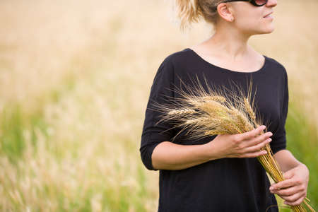 Portrait of smiling woman with ears of wheat walking in the field on sunny summer day. Harvest.