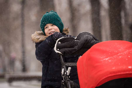 niño empujando: Portrait of cute happy kid boy in winter clothes pushing stroller with his siblling. Child with baby carriage outdoors on a cold day. Family concept