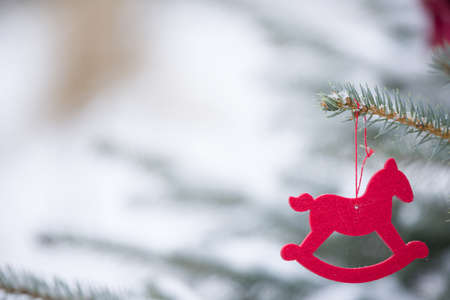 Nice red decoration - red horse - hanging on a Christmas tree branch outdoors on a sunny day. Winter. Holidays concept