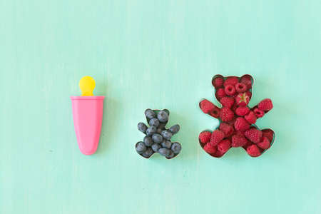 bear berry: Teddy bear shaped molds for the cookies full of fresh organic raspberries and pink popsicle form for sorbet on turquoise background.