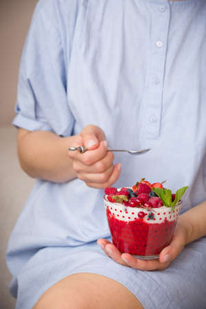 Woman  holding smothie bawl with organic yogurt, berries and mint. Homemade yogurt in girls hands served with raspberry, strawberry and blueberry. Breakfast. snack. Healthy eating, lifestyle concept