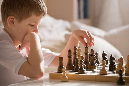 Jongen speelt schaak in de kamer. Weinig slimme jongen geconcentreerd en na te denken tijdens het spelen Schaken thuis.