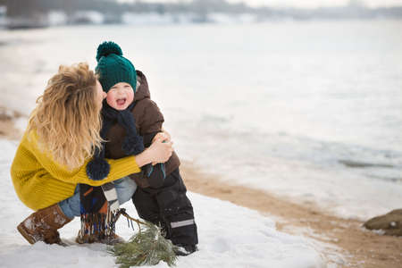 chrstmas: Portrait of young woman hugging her adorable little toddler boy on a winter cold day. Mother and child walking by river and having fun. Happy family outdoors. Winter, Christmas and lifestyle concept