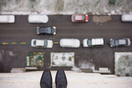 instability: Close-up of mans feet standing on the edge of the roof. Top view on mans boots on the balcony of high building. Depression and instability concept. Crisis. Stock Photo