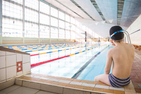 Cute Little Boy Ready To Dive In The Sport Swimming Pool. Indoors. Sport  Activities