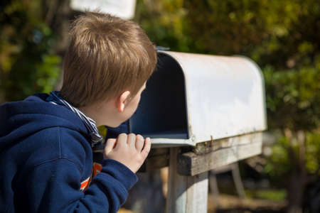 School boy opening a post box and checking mail. Kid waiting for a letter, checking correspondence and looking into the in the metal mailbox. Banco de Imagens