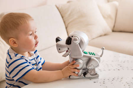 Adorable toddler boy playing with interactive toy. Child with toy robot dog. indoors. Activities for small children. Communication and digital concept.