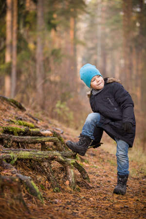 sitting on the ground: Cute kid boy walking in the forest on a cold autumn day. Child outdoors. Lifestyle concept Stock Photo