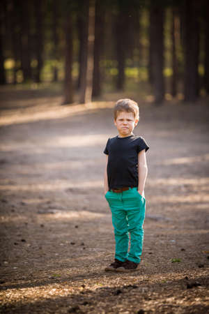 Disappointed upset little kid boy pinching his nose. close up outdoor. A cute boy in a green trousers and a grimace on his face standing in a pine forest. Sunny day. Stock Photo