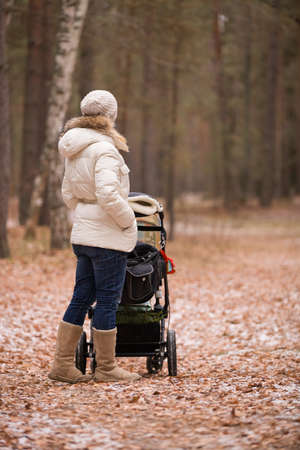 niño empujando: Young woman walking with a stroller in the forest. Mother with a child. Girl with carraige ourdoors. Lifestyle concept