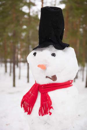 Portrait de drôle bonhomme de neige à la main avec chapeau haut de forme, pipe et écharpe rouge. Fond de forêt d'hiver.