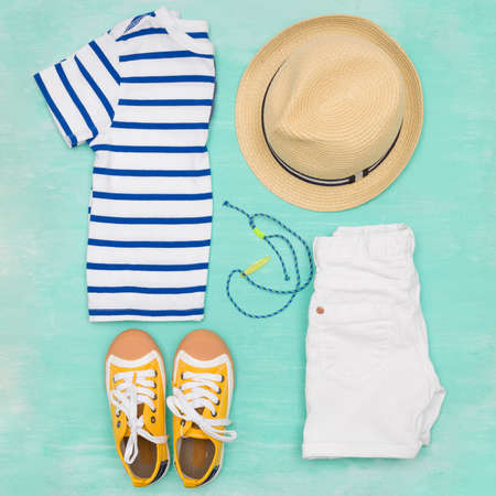 Child's striped t-shirt, demin shorts, accessories, yellow shoes and straw hat on turquoise wooden background. Top view. Flat lay. Kid's summer clothes collage