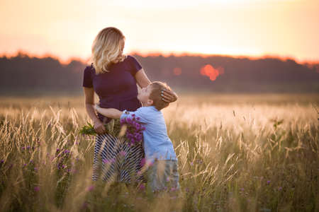 Cute kid boy hugging his mother on a summer meadow on beautiful summer sunset. Happy family together. Mum and child. Motherhood and childhood. Family walking in the field. Outdoors.