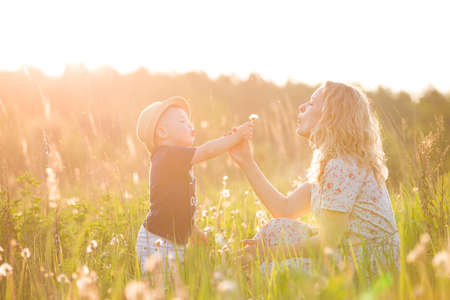Cute little toddler boy in a straw hat holding his mothers hand and blowing dandelion. Adorable child walking with his mom in park on sunny summer day. Family on sunset. Childhood, motherhood concept Stock Photo