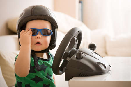 Cute little kid boy in a helmet playing with Computer steering wheel. Future driver. Getting ready for professional driving. Child driving a car. Funny toddler boy indoors. Boy and a car. Standard-Bild