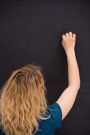 Young girl drawing on a black background. Business woman writting on the board. Teacher hand drawing on chalkboard. Education and idea concept.