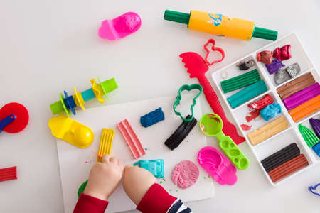 Childs hands with colorful clay. Toddler playing and creating toys from play dough. Boy molding modeling clay. Stock Photo