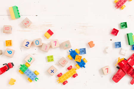 Top view on wooden cubes with numbers and colorful toy bricks on a white wooden background. Toys in the table