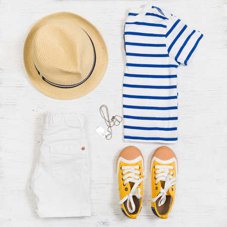 Childs striped t-shirt, demin shorts, accessories, yellow shoes and straw hat isolated on white background. Top view. Flat lay. Kids summer clothes collage Imagens