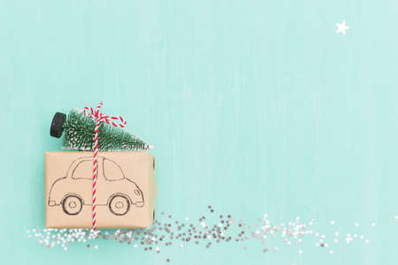 Top view on Christmas gift wrapped in craft gift paper decorated with car drawing  with Christmas tree on turquoise wooden background with sparkling stars. New Year, holidays and celebration concept+