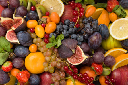 Top view on mixture of different fruit and berries: lemons, figs, grapes, tangerines, apples, strawberry, plums, red current, oranges. Healthy food concept