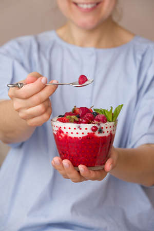 Woman  holding smoothie bawl with organic yogurt, berries and mint. Homemade yogurt in girls hands served with raspberry, strawberry and blueberry. Breakfast. snack. Healthy eating, lifestyle concept