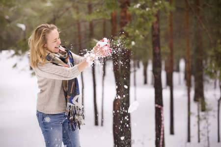 Snow in hands of a young blond woman with red manicure, warm sweater and yellow scarf. Winter walks outdoors. Snow in the forest.