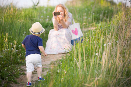 그녀의 사랑스러운 작은 유아 소년 스마트 폰의 사진을 복용하는 어머니. 가족 공원에서 산책입니다. 엄마와 함께 작은 아이.
